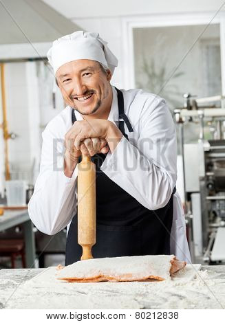 Portrait of happy chef holding rolling pin at counter while preparing pasta in commercial kitchen