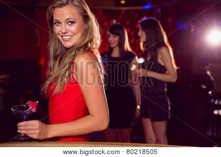 Pretty girl drinking a cocktail at the nightclub