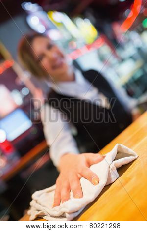 Pretty barmaid wiping down bar in a bar