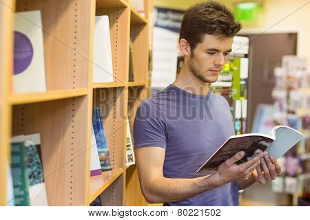 University student standing reading textbook in the bookcase at the university