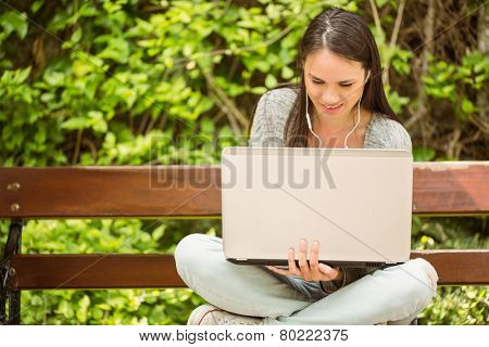 Smiling student sitting on bench listening music and using laptop in park at school