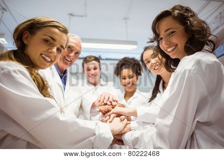 Science students and lecturer putting hands together at the university