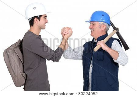 Builder shaking hands with young apprentice