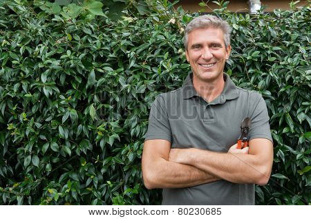 Portrait Of Mature Man Looking At Camera Standing In Front Of Hedge