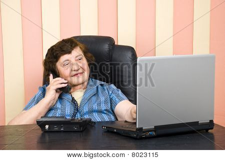 Elderly Executive Using Laptoop And Talk By Phone