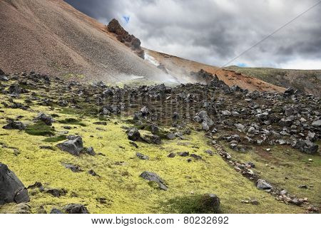 Iceland in July. Rhyolitic mountains smoke underground heat. In hollows last year's snow lie