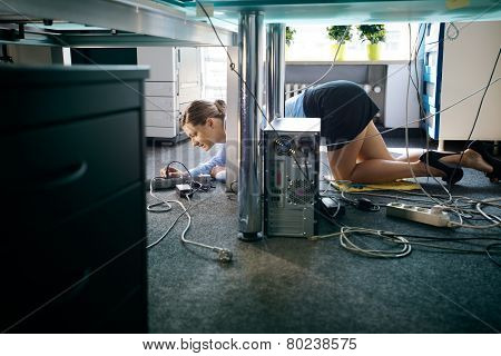 Young Worker Connecting Cables And Wires To Computer In Office