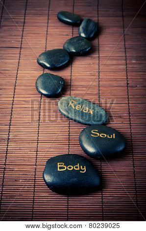 Black massage stones with words body, soul and relax on the brown mat