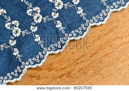 Jeans Fabric With White Flower Embroidery Laid Over Plywood Background