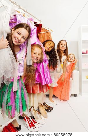 Happy small girls in store standing among dresses