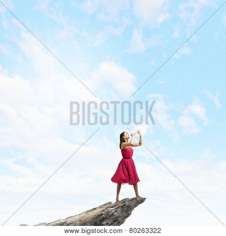 Young pretty woman in red dress playing flute