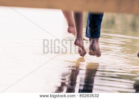 Close up of people's feet sitting on bridge