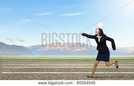 Young businesswoman in paper crown running in a hurry