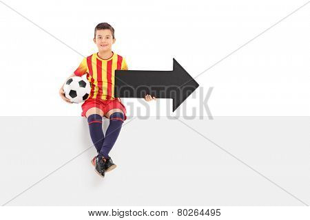 Junior athlete holding an arrow and a football seated on a bank signboard isolated on white background