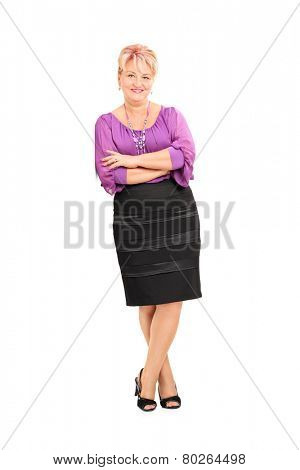 Full length portrait of an elegant mature woman leaning against a wall isolated on white background