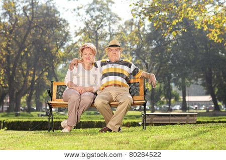 Lovely mature couple relaxing in park seated on a bench