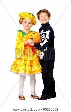 Full length portrait of a cute kids wearing halloween costumes stand with pumpkin. Halloween. Isolated over white.