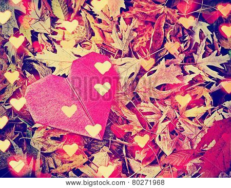 an origami heart and leaves as a background with bokeh added in an overly toned with a retro vintage instagram filter effect