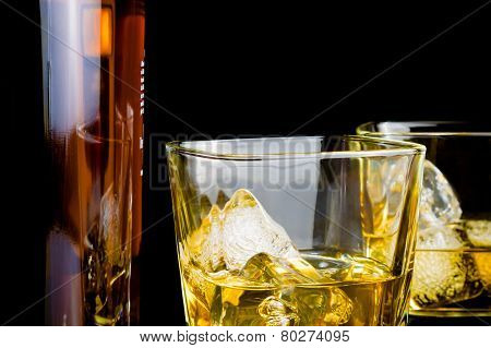 Whiskey With Ice In Glasses In Front Of Bottle On Black Background