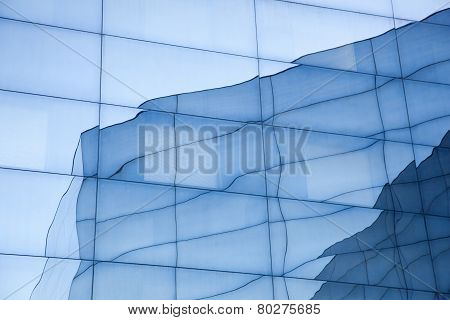 Facade Of Modern Glass Building With Reflections Of Blue Sky And Glass Wall