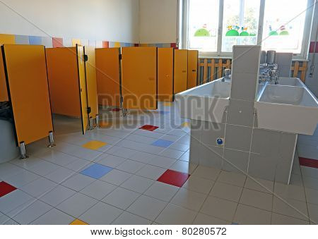 Bathroom Of The Nursery School With White Ceramic Sinks And Doors Yellow