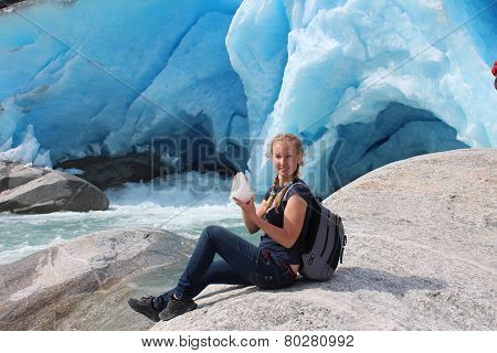 Young woman on the Nigardsbreen, sitting with piece of ice. Glacier in Norway.