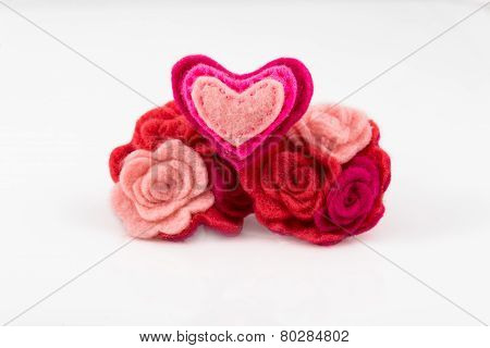 Wool heart with pink and red flowers on white background. Valentine's Day greeting card.