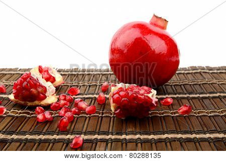Studio Shot Open Pomegranate On Brown Wooden Mate