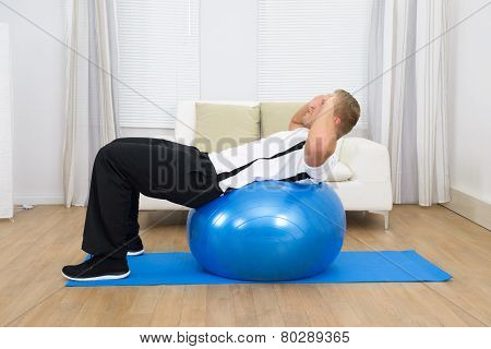 Man Leaning On Pilates Ball Doing Exercise