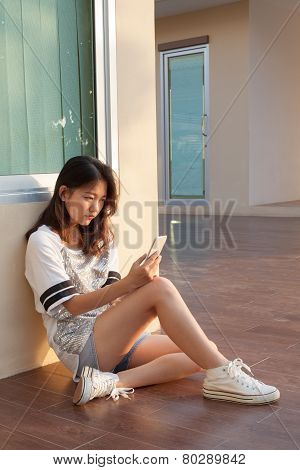 Portrait Of Teen  With Serious Face Looking And Reading Message On Mobile Phone By Unhappy Face