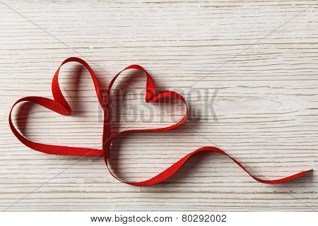 Two Hearts Shape On White Wooden Background. Valentine Day Or Wedding Love Concept. Ribbon As Joined
