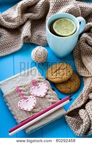 A Cup Of Tea In Sweater With Lemon, Old Notebook With Hearts Of Felt, Beige Knitted Blanket And Spok