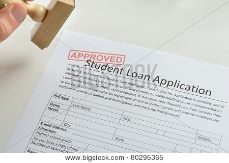 Person Hand With Stamp And Approved Loan Application