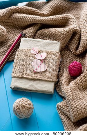 One Old Notebook In Knitted Cover With Felt Hearts Lie Next To The Coil Bright Filaments And Blanket