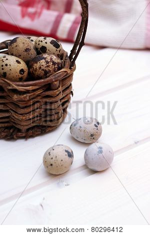 Quail Eggs In A Wicker Basket On A Wooden Background With Kitchen Towel