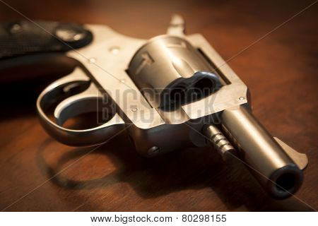 A close-up of a .32 caliber pistol on a brown wooden table, shallow depth of field.