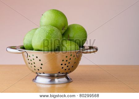 Green apples in a colander