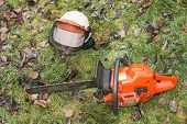 foto of chainsaw  - Chainsaw and helmet lying on the ground - JPG