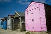 picture of beach hut  - 5 brightly colored beach huts against a blue sky on a sunny day at West Wittering beach - JPG