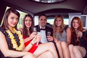 foto of limousine  - Happy friends drinking champagne in limousine on a night out - JPG