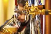 stock photo of dispenser  - Pouring beer to a glass in a restaurant - JPG
