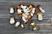 stock photo of edible mushroom  - edible mushroom fungi boletus in heart form basket on old wooden table - JPG