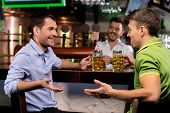 image of bartender  - Two young man drinking beer and talking to each other while bartender tapping beer on the background - JPG