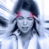 stock photo of deprivation  - Young woman with a pounding headache or migraine standing clutching her temples with an expression of pain - JPG