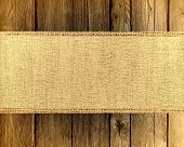 picture of wood craft  - Burlap jute canvas banner textured with dark wood background - JPG