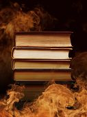 stock photo of vapor  - Pile of hardcover books surrounded with swirling tendrils smoke or vapor in a darkened vintage style room conceptual of magic - JPG