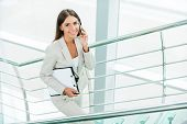 stock photo of bannister  - Beautiful young businesswoman in formalwear talking on the mobile phone and smiling while moving up by staircase - JPG