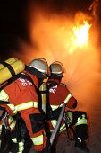 stock photo of firefighter  - Delete two firefighters a burning gas line - JPG