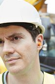 stock photo of noise pollution  - Male Construction Worker Wearing Protective Ear Plugs - JPG