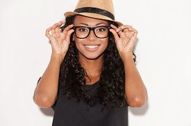 pic of shot glasses  - Portrait of beautiful young African woman in glasses and funky hat adjusting her glasses and smiling while standing against white background - JPG